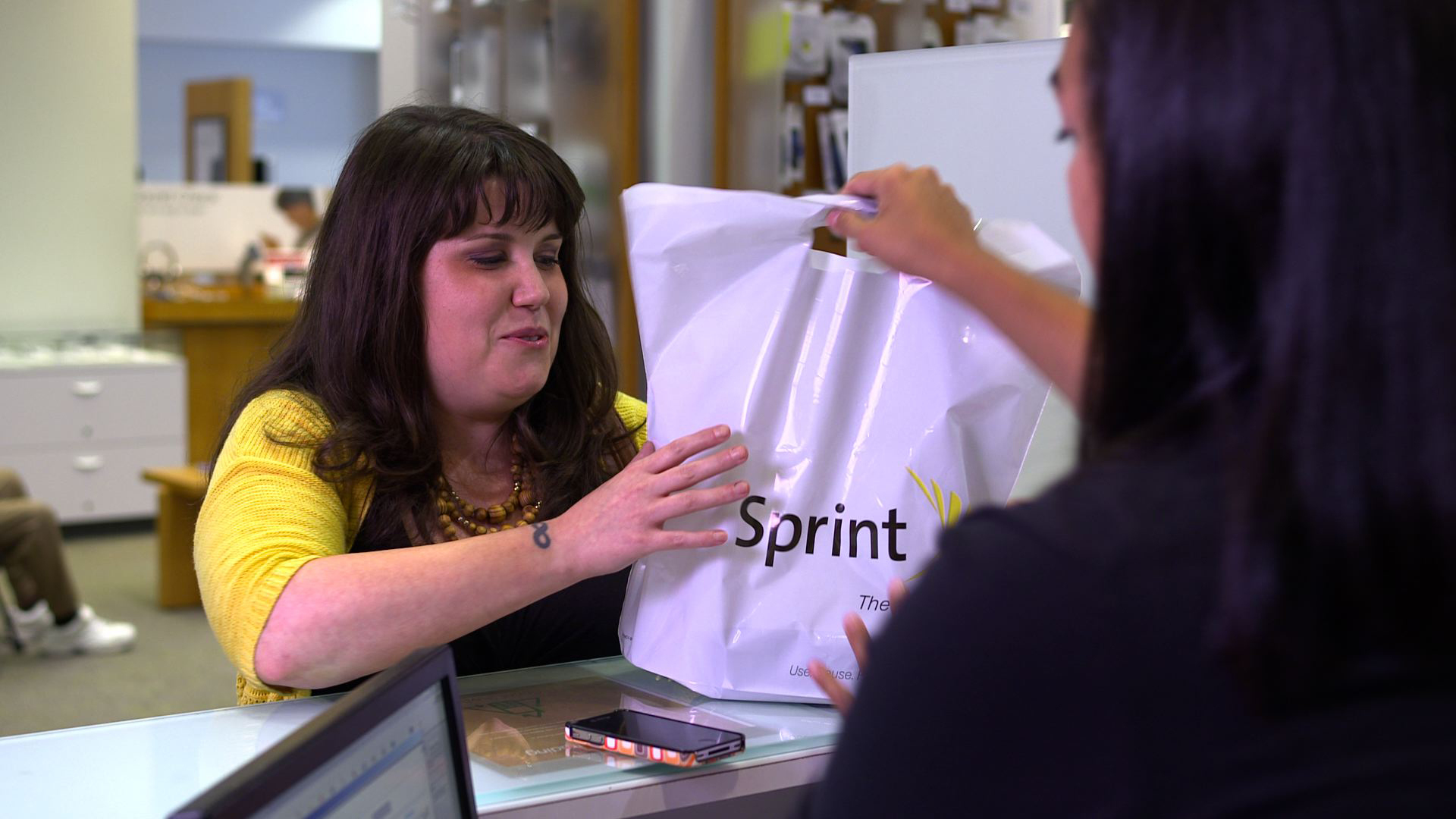 A Sprint customer takes advantage of the buyback program in a Sprint retail store in Chicago, IL. Last year alone, Sprint put more than $100 million back in customers' pockets through their trade-in program. (Photo: Business Wire)
