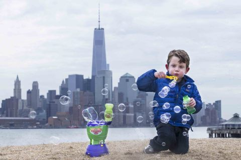 Benjamin Winston, 4, blows bubbles alongside the Typhoon 2.0 bubble machine and against the backdrop of New York City as he prepares for National Bubble Week, an event celebrated by Gazillion Bubbles to herald the arrival of spring, Friday, March 14, 2014, in Hoboken, N.J. (John Minchillo/AP Images for Gazillion Bubbles)