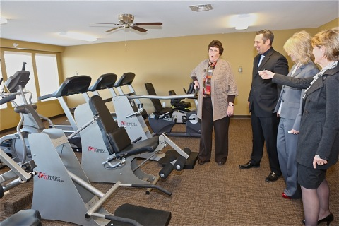 Fort Collins Mayor Karen Weitkunat tests out the fitness equipment at the Legacy Senior Residences, a new affordable-housing community for senior citizens, during a ribbon-cutting and grand-opening event today. The $14.7 million 72-unit development was funded in large part through a $13 million investment by UnitedHealth Group, including its Optum and UnitedHealthcare businesses, in Colorado. The company teamed up with U.S. bank for the tax credit partnership. Additional partners included the Cornerstone Development, the City of Fort Collins, the Fort Collins Housing Authority and the Colorado Housing and Finance Authority. L to R: Mayor Weitkunat; Matt Zarlengo, U.S. Bank; Bobbi Jo Lucas, Cornerstone Associates; and Jan Eyer, Optum of Colorado (Photo: Craig Vollmer).