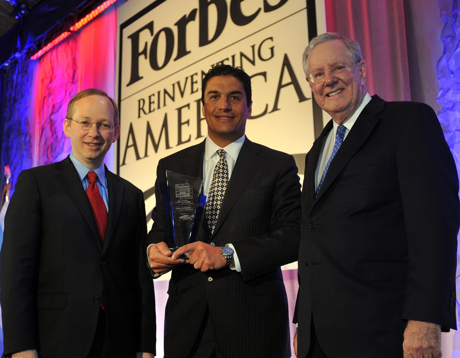 """David Steel (left), Executive Vice President of Samsung Electronics North America, presents the Forbes Excellence Award for Education to Aragon Burlingham (center), Founder and President of We Teach Science Foundation, at the inaugural Forbes Reinventing America Summit held in Chicago, IL, March 26-March 28, 2014, and hosted by Steve Forbes (right), Chairman and Editor-in-Chief of Forbes Media. """"Samsung applauds Mr. Burlingham's efforts to build a bridge between public school students and private sector STEM professionals to help American students succeed,"""" said David Steel. (Photo: Business Wire)"""