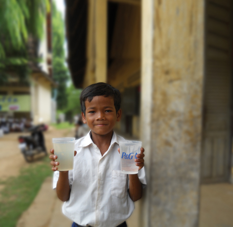 Kosol, aged 11 from Cambodia holds the before and after of a cup of water purified with a P&G packet. (Photo: Business Wire)