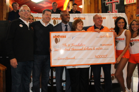 Hooters presents a $200,000 check to The V Foundation for Cancer Research at the Hooters of West End in Dallas during the excitement of the men's college basketball tournament finals. (L-R: Mike Burkey, Director of Operations, Hooters Texas Division; Bruce Skala, Vice President of Marketing, Hooters of America; Jay Williams, ESPN analyst; Susan Braun, CEO, The V Foundation; Dick Vitale, ESPN analyst and board member of The V Foundation; Marissa Raisor, Miss Hooters International) (Photo: Business Wire)