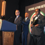 "AHF President Michael Weinstein (at podium) accepts a ""Keepers of the Dream"" award from Rev. Al Sharpton (back left) and Rev. Dr. W. Franklyn Richardson, Nation Action Network Chairman (back right, holding award) at the 16th annual ""Keepers of the Dream"" awards gala in New York City on April 9, 2014 (Photo: Business Wire)"