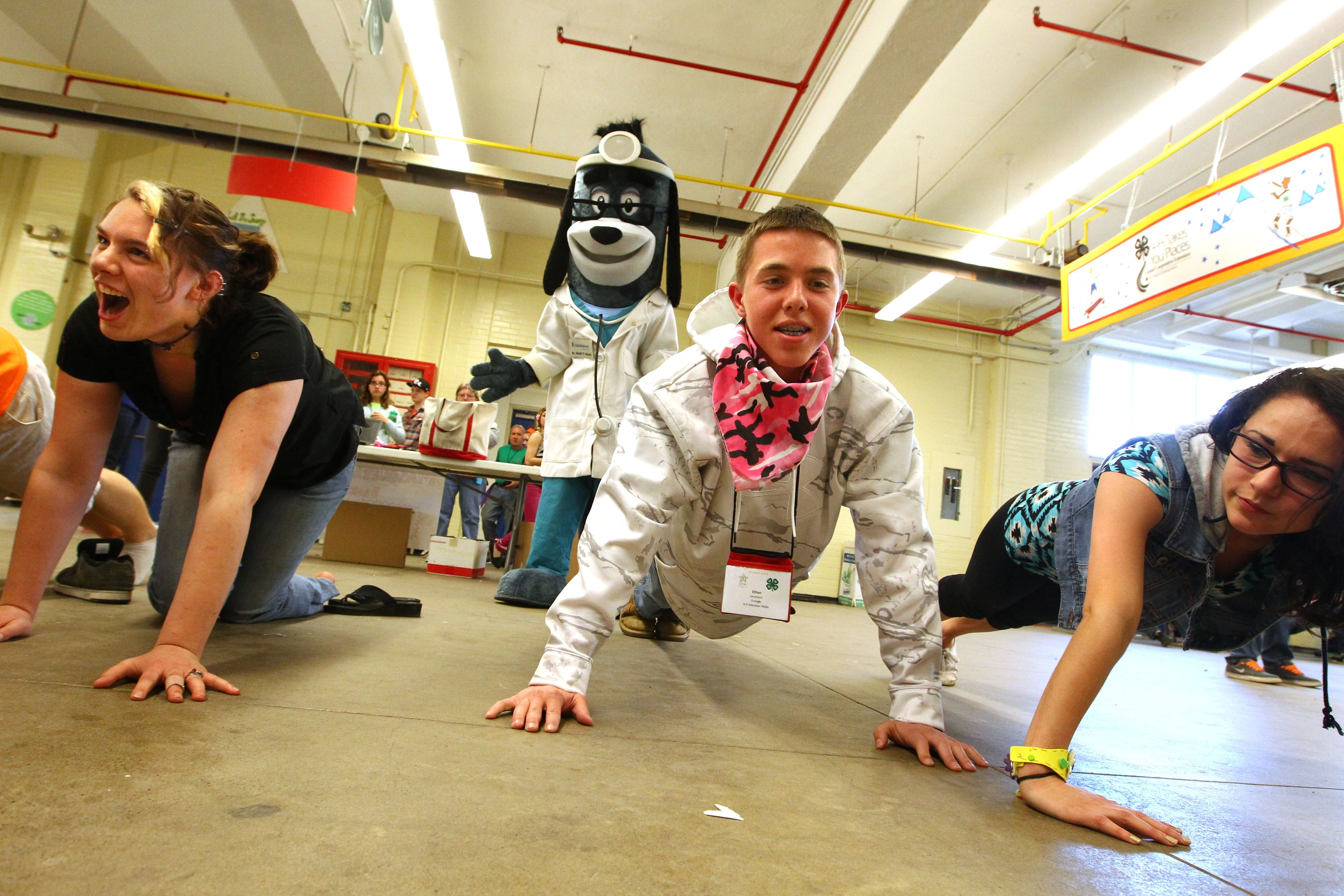 """UnitedHealthcare mascot Dr. Health E. Hound watches Ethan Jacobsen, of Newburgh, N.Y., Orange County, do push-ups. He was participating in interactive stations based on the """"Choose Health: Food, Fun, and Fitness"""" curriculum created in the Division of Nutritional Sciences at Cornell University. Youth also had the opportunity to make their own healthy smoothies with renewable energy bikes equipped with specially installed pedal-powered blenders at the New York State Fairgrounds in Syracuse, N.Y., on Saturday, April 12, 2014. (Photos by Michael J. Okoniewski)"""