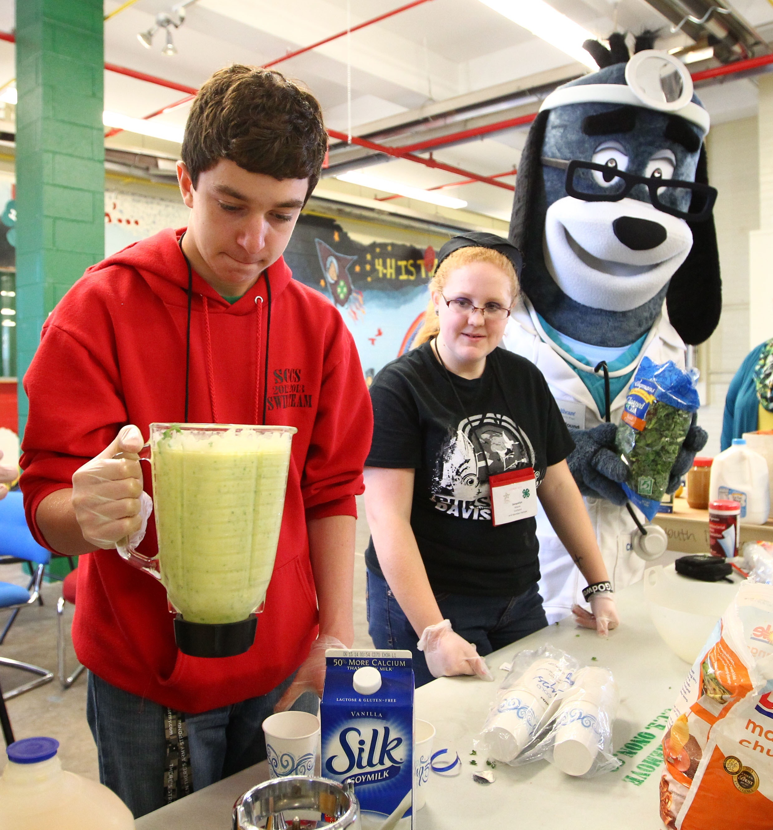 """Ben Davis, left, and Jacquelyn Moroe and UnitedHealthcare's mascot, Dr. Health E. Hound, make a healthy smoothie. Davis is from Moravia, Cayuga County, while Moore is from Marathon, Cortland County. They participated in interactive stations based on the """"Choose Health: Food, Fun, and Fitness"""" curriculum created in the Division of Nutritional Sciences at Cornell University. 4-H Youth also had the opportunity to make their own healthy smoothies with renewable energy bikes equipped with specially installed pedal-powered blenders at the New York State Fairgrounds in Syracuse, N.Y., on Saturday, April 12, 2014. (Photos by Michael J. Okoniewski)"""