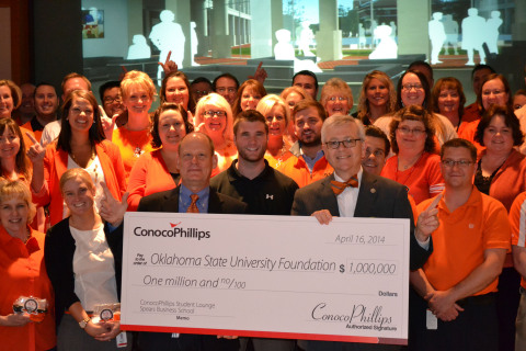 ConocoPhillips announced a $1 million donation toward building a new home for Oklahoma State University's Spears School of Business. During an event in Bartlesville, Okla., Ken Seaman (pictured left holding check), ConocoPhillips' executive sponsor for OSU and a university alum, presented a check for $1 million to OSU's Dr. Ken Eastman (pictured right holding check), interim dean and associate professor of management, Spears School of Business. They are joined by some of the 440 ConocoPhillips employees who are OSU alumni. (Photo: Business Wire)