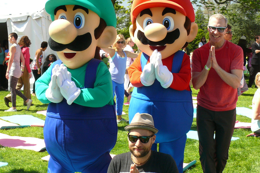 "In this photo provided by Nintendo of America, Mario and Luigi join MC Yogi from San Francisco and Roger R. from Houston for a yoga session during the 136th annual White House Easter Egg Roll on April 21, 2014, in President's Park (one of America's 401 national parks!) Nintendo joined with the National Park Foundation to offer guests the opportunity to play Wii Fit U and Wii Sports Club, two active games that align with this year's event theme, ""Hop Into Healthy, Swing into Shape,"" which encourages children and families to live healthier and more active lifestyles. (Photo: Business Wire)"