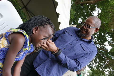 Forest Whitaker, Academy Award winner and UNESCO Goodwill Ambassador for Peace, fits a young girl with hearing aids at a Starkey Hearing Foundation mission in Kampala, Uganda in March. (Photo: Business Wire)