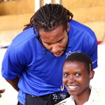 Larry Fitzgerald, Arizona Cardinals wide receiver, fits a patient with hearing aids at a Starkey Hearing Foundation mission in Butare, Rwanda in March. (Photo: Business Wire)