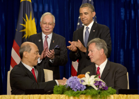 President Barack Obama, standing right, and Malaysian Prime Minister Najib Razak, standing left, applaud as Bill Radany, president & CEO of Verdezyne, right, and Tan Sri Dato' Seri Mohd Bakke Salleh, President & Group Chief Executive of Sime Darby Berthed, left, participate in the signing of major commercial agreements with American businesses at the Ritz-Carlton in Kuala Lumpur, Malaysia, Monday, April 28, 2014. (AP Photo/Carolyn Kaster)