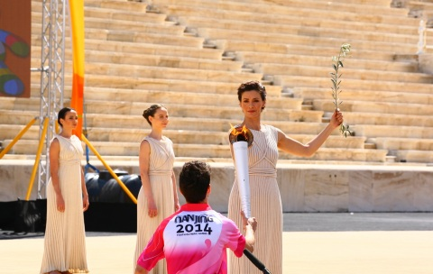 The High Priestess Katerina Lehou is holding the Youth Olympic Flame and passing on to the first tor ...