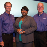 Steve Nieman, senior vice president of Tyler's Local Government Division, and Brett Cate, president of Tyler's Local Government Division, present a Tyler Excellence Award to Dunwoody's Municipal Court Administrator Trina Gallien. (Photo: Business Wire)
