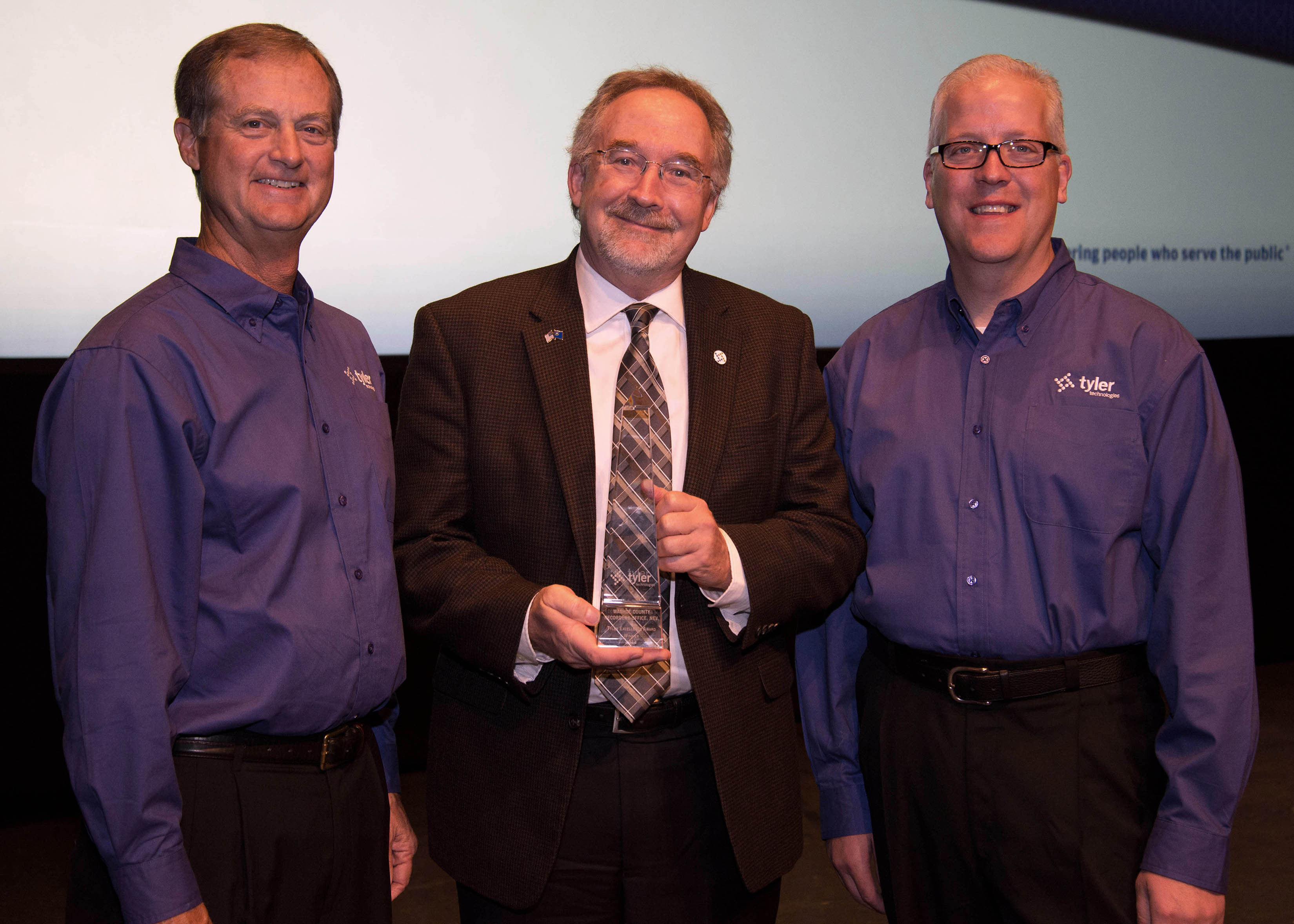 Steve Nieman, senior vice president of Tyler's Local Government Division, and Brett Cate, president of Tyler's Local Government Division, present a Tyler Excellence Award to Washoe County's Recorder Larry Burtness. (Photo: Business Wire)