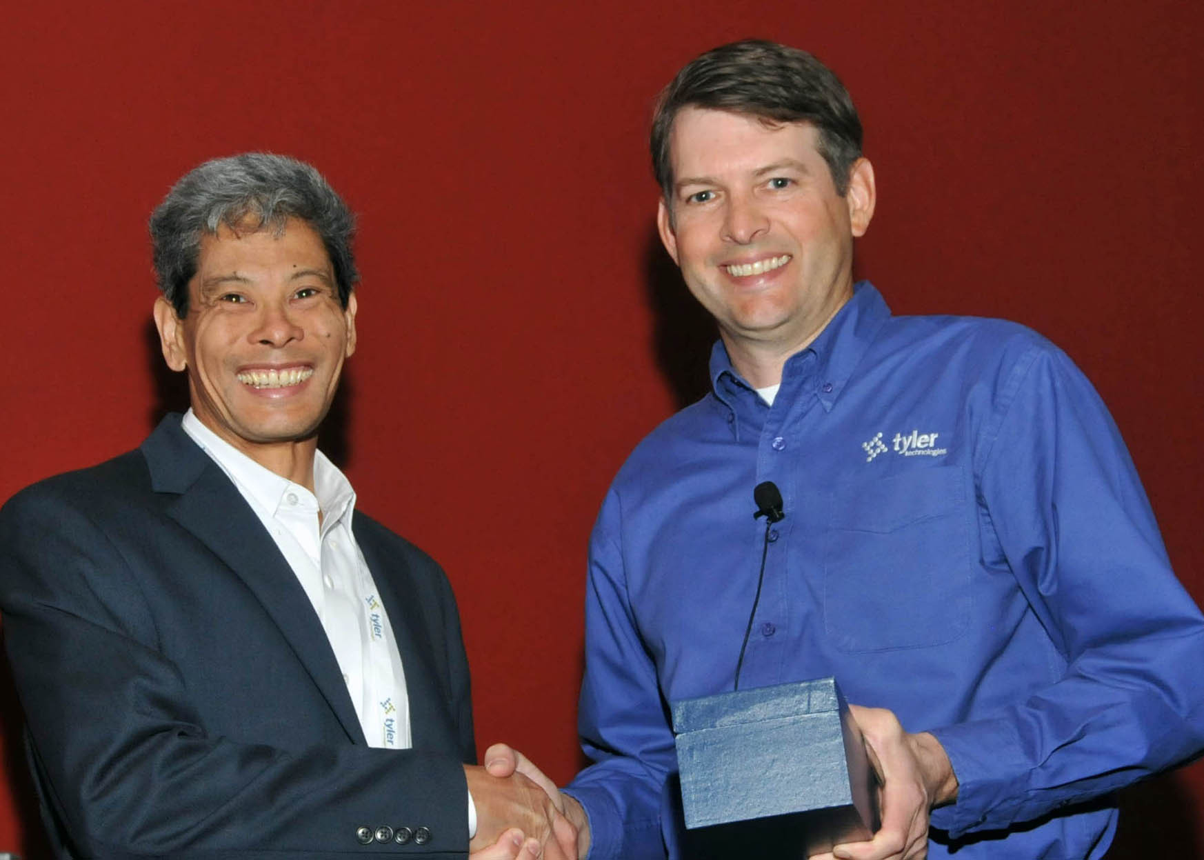 Desmond Chin, finance director at the village of Palmetto Bay, accepts a Tyler Excellence Award from Jeff Green, senior vice president at Tyler. (Photo: Business Wire)
