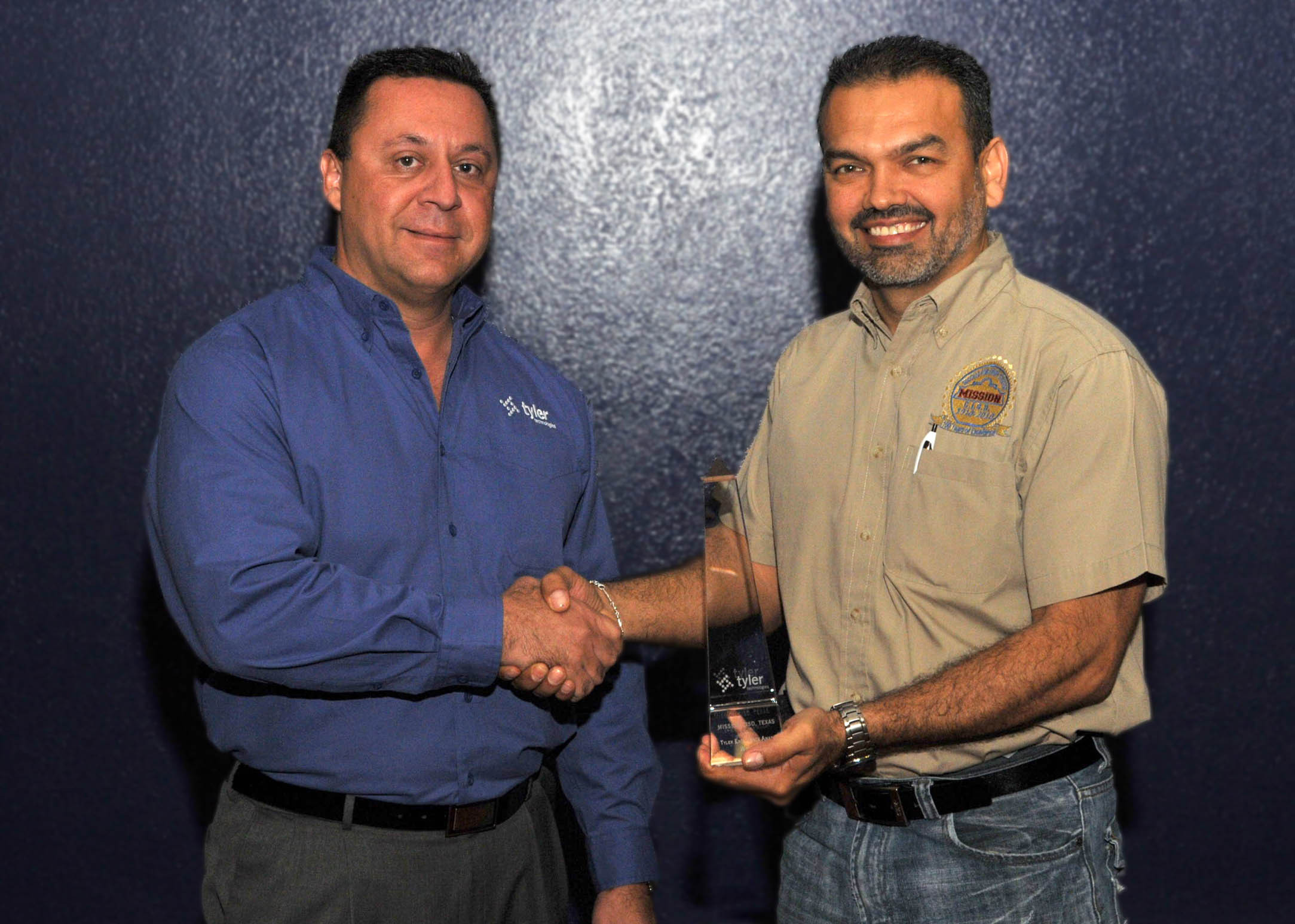 Jorge Cavazos, administrator for information systems at Mission Consolidated Independent School District, accepts a Tyler Excellence Award from Nick Botonis, president of Tyler SIS. (Photo: Business Wire)