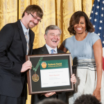 Mystic Aquarium/Sea Research Foundation President and CEO Stephen M. Coan (C) and University of Rhode Island graduate student Justin Richard (L), who is doing his research at Mystic Aquarium, accept the National Medal for Museum and Library Service from First Lady Michelle Obama, May 8, 2014, at the White House in Washington, D.C. (Photo: Business Wire)