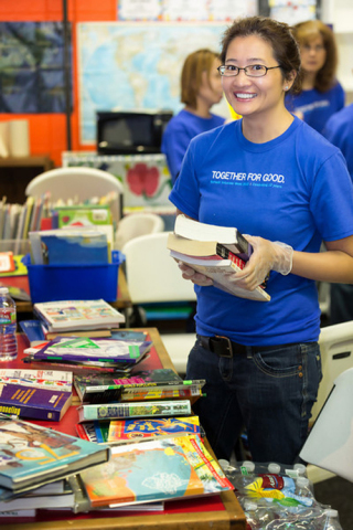 Julie Wiegand organizes books and games at the Boys & Girls Club of Denver during Schwab Volunteer W ...
