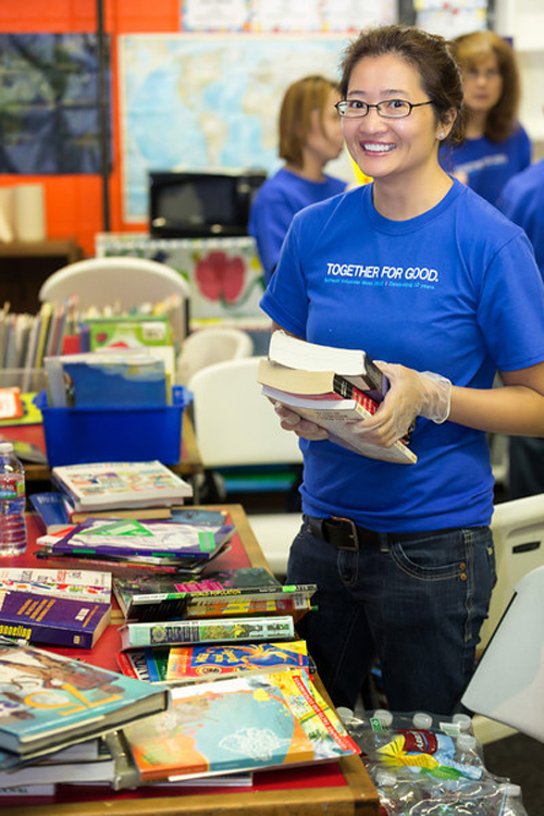 Julie Wiegand organizes books and games at the Boys & Girls Club of Denver during Schwab Volunteer Week. (Photo by Greg Roe)