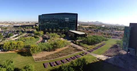 "University of Phoenix volunteers ""plant"" 10,000 flags spelling ""FREEDOM IS NEVER FREE"" to honor the sacrifices made by active-duty service members, their families and veterans for the Memorial Day weekend. (Photo: Business Wire)"