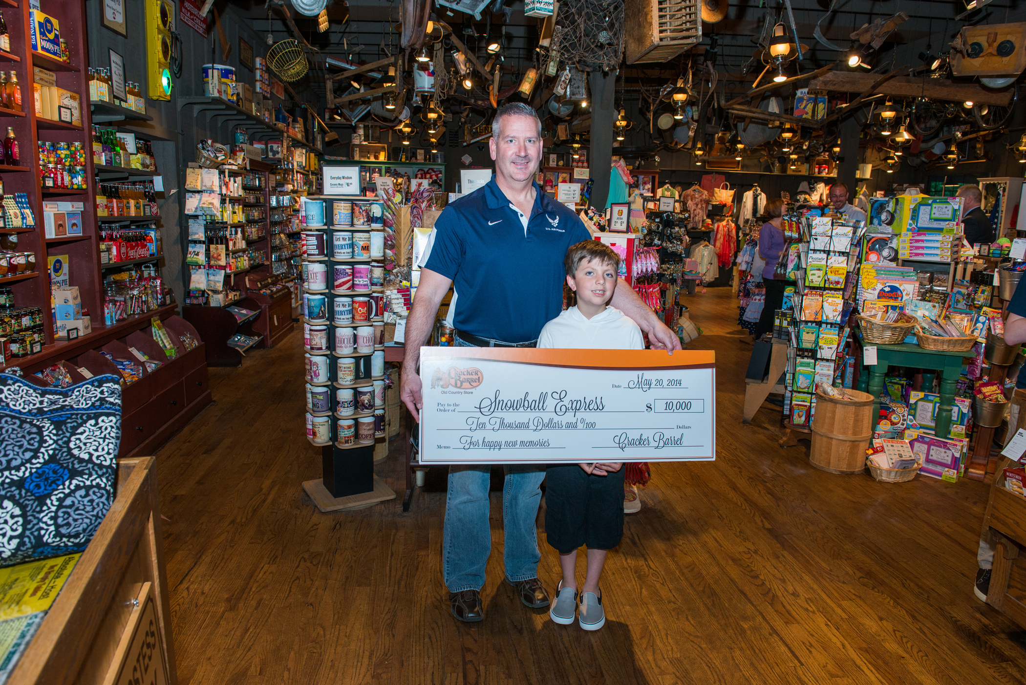 Snowball Express assists military families who have lost a parent killed during active duty. Accepting the Cracker Barrel contribution are Lt. COL. Frank Daily and eight year old Myles Eckert. Last February, Myles found a $20 bill in this Maumee, Ohio Cracker Barrel store's parking lot and generously gave the money to Lt. Col. Dailey, who was in the restaurant that day with his family. Myles father was killed by a roadside bomb in 2005. (Photo: Business Wire)