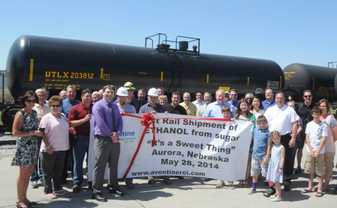 "May 28 was a banner day as Aventine Renewable Energy Inc. held a ribbon-cutting ceremony celebrating its first railcar shipment of ethanol produced at its Aurora West facility in Aurora, Neb., using sugar-based only feedstock. Plant Manager Chad Campbell (in front of banner) cut the ribbon. Joining him were Aventine CFO Brian Steenhard (behind word ""Rail"" on banner) and Aventine President and CEO Mark Beemer (standing behind the banner with one of his sons) along with other employees and family members. (Photo courtesy of Aurora News-Register)"