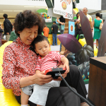 "In this photo provided by Nintendo of America and released June 7, 2014, Ronghua W., 64, of China and her granddaughter Sophia X., 2, of Los Angeles, enjoy playing ""Donkey Kong Country Returns 3D"" at the Westfield Culver City mall on June 6, 2014. The free three-month ""Play Nintendo Tour 2014"" kicked off in Los Angeles on June 6 and will visit malls and events in a dozen major cities across the United States, showcasing games that feature kid-friendly characters like Donkey Kong, Mario and Kirby, all played on Nintendo 2DS, the latest member of Nintendo's hand-held family. (Photo by Nintendo/Bob Riha, Jr.)"