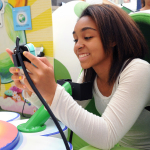 "In this photo provided by Nintendo of America and released June 7, 2014, Teoko P., 17, of Los Angeles plays ""Yoshi's New Island"" in a Yoshi egg-shaped seat at the Westfield Culver City mall on June 6, 2014, as part of the ""Play Nintendo Tour 2014,"" which kicked off in Los Angeles on June 6. The free three-month tour will visit malls and events in a dozen major cities across the United States. Nintendo 2DS is an ideal first-time system. (Photo by Nintendo/Bob Riha, Jr.)"