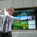 A Wall Street passerby swings through Mohegan Sun's Interactive golf-themed advertising campaign. (Photo: Business Wire)