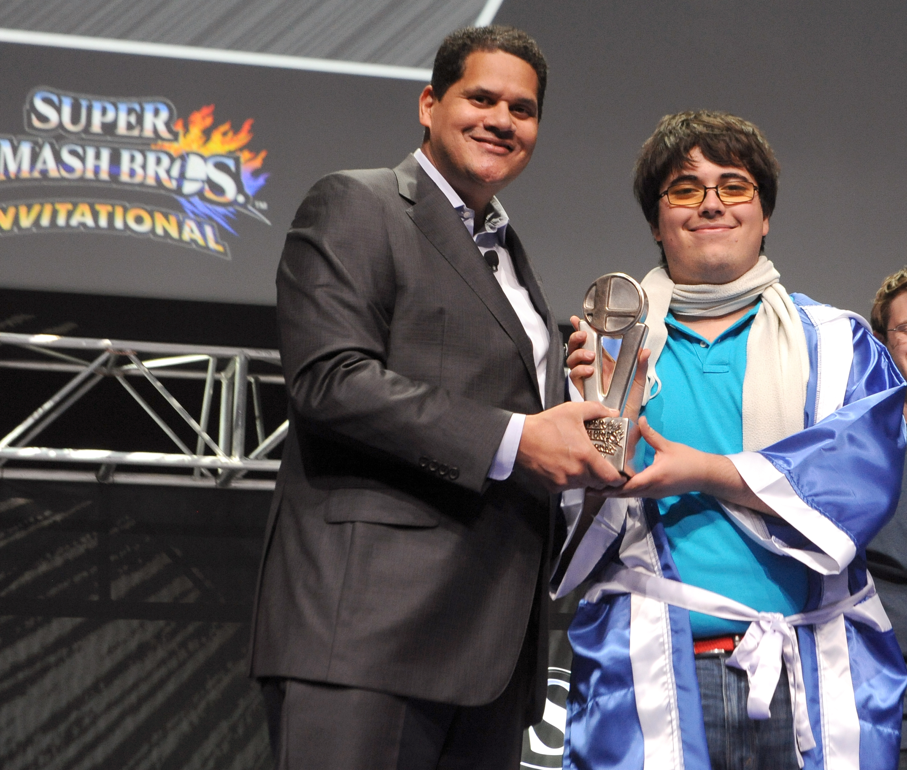 """In this photo provided by Nintendo of America, Super Smash Bros. Invitational winner Gonzalo """"ZeRo"""" Barrios of Chillan, Chile receives the grand-prize trophy from Nintendo of America President and COO Reggie Fils-Aime. Thousands of fans in the audience and countless more watching online celebrated the Super Smash Bros. franchise in anticipation of the game's launch this year on both Nintendo 3DS and Wii U. (Photo: Business Wire)"""