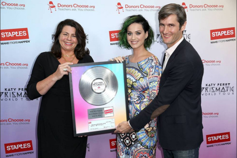 """Alison Corcoran, senior vice president of marketing for Staples, and global pop music superstar, Katy Perry, present DonorsChoose.org's founder and CEO, Charles Best, with a commemorative platinum record celebrating Staples' $1 million donation as part of the """"Make Roar Happen"""" campaign on June 12th, 2014 at NOKIA Theatre L.A. Live. Staples donated these funds to further its commitment to education and support classroom projects throughout the U.S. (Photo by Matt Sayles/Invision for Staples/AP Images)"""