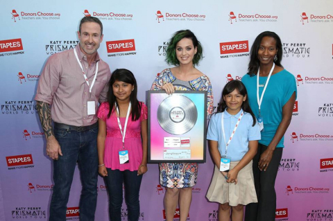"""Katy Perry poses with students and teachers from local LA elementary schools at the Staples """"Make Roar Happen"""" press conference held on Thursday, June 12th, 2014 at NOKIA Theatre L.A. Live. Staples continued its commitment to education by donating $1 million dollars to DonorsChoose.org to support classroom projects. (Photo by Matt Sayles/Invision for Staples/AP Images)"""