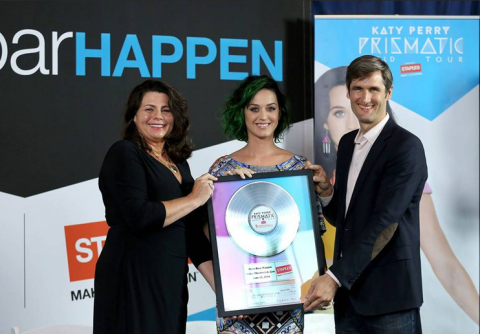 "Alison Corcoran, senior vice president of marketing for Staples, and global pop music superstar, Katy Perry, present DonorsChoose.org's founder and CEO, Charles Best, with a commemorative platinum record celebrating Staples' $1 million donation as part of the ""Make Roar Happen"" campaign on June 12th, 2014 at NOKIA Theatre L.A. Live. Staples donated these funds to further its commitment to education and support classroom projects throughout the U.S. (Photo by Matt Sayles/Invision for Staples/AP Images)"