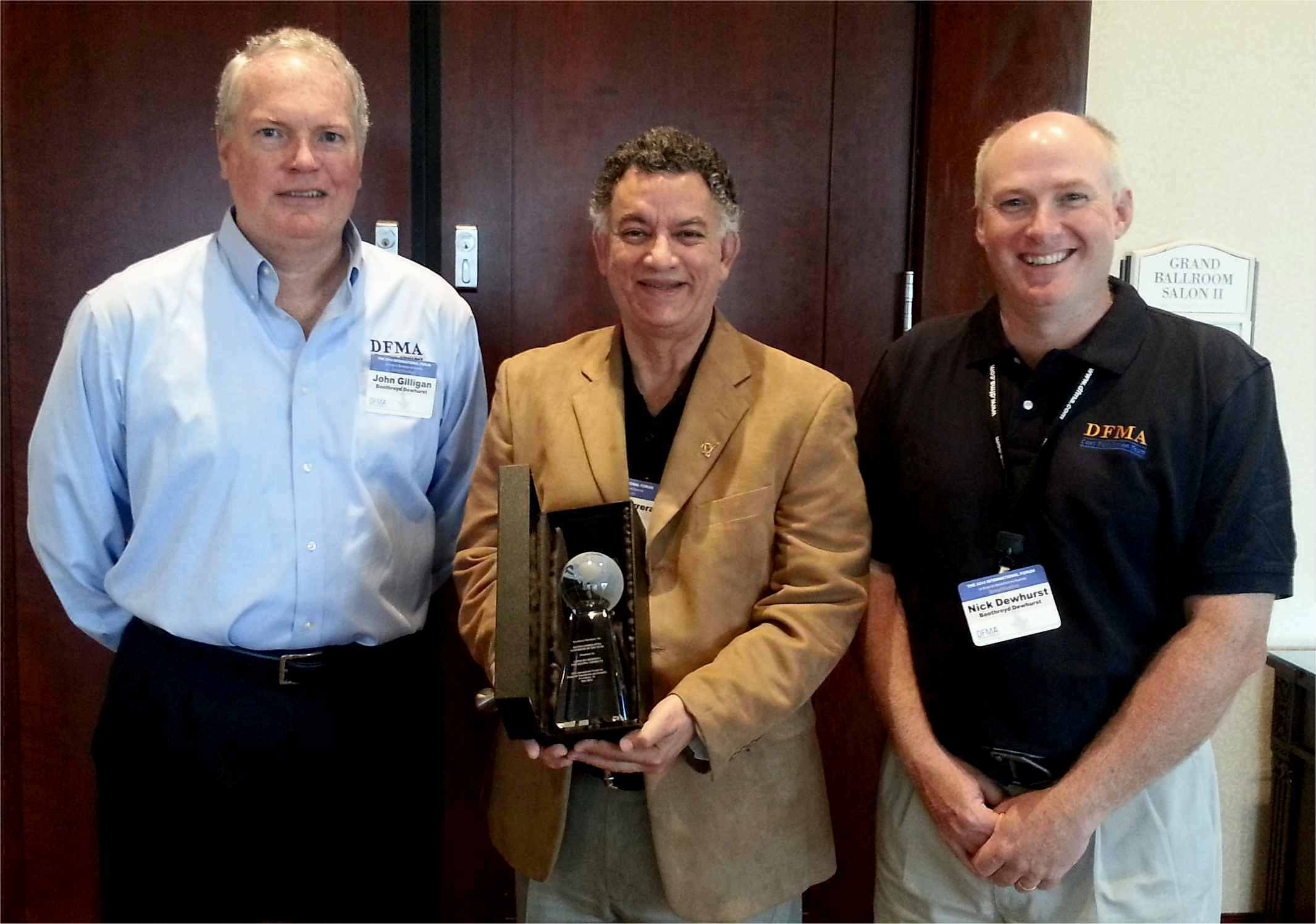 """Receiving the """"Distinguished DFMA Supporter of the Year Award"""" at the June 2014 DFMA Forum in Providence, RI, is Dr. Alfredo Herrera (center), The Boeing Company's Mesa Lean+ Engineering Project Manager. Standing to Herrera's left and right are Boothroyd Dewhurst, Inc. President John Gilligan and Executive Vice President Nick Dewhurst. (Photo: Business Wire)"""