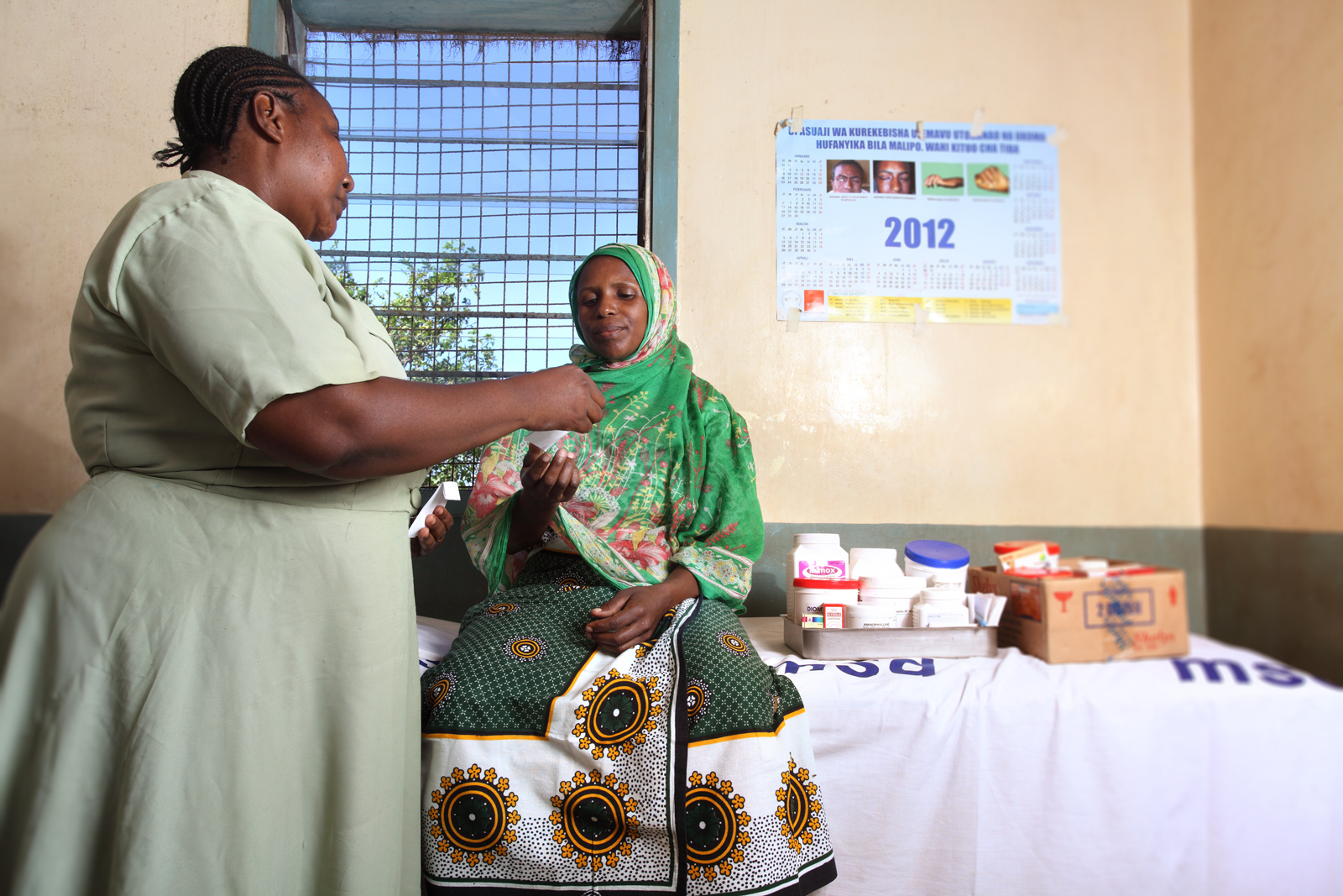 A nurse from a clinic in Dar es Salam District, Tanzania, dispenses medicine to a patient, Optuna John. Since Project Last Mile launched in 2010, Medical Stores Department's distribution system has expanded to include delivery to more than 5,500 health facilities. Previously, Medical Stores Department delivered to approximately 150 district warehouses, thus losing sight of the last mile. Now, people like Optuna can receive medical care that was not readily accessible in the past. (Photo: Business Wire)