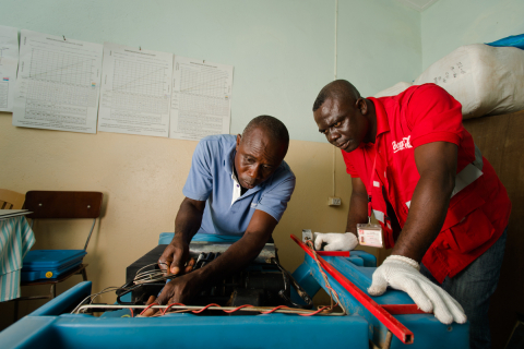 Coca-Cola Lead Cooler Technician, Maxwell Ayisi (right), and Ghana Health Service Refrigeration Technician, Livingstone Modey (left), repairing a dual gas/electric cooler used to store vaccines at a clinic in Peki Dzake in the Volta Region of Ghana. (Photo: Business Wire)