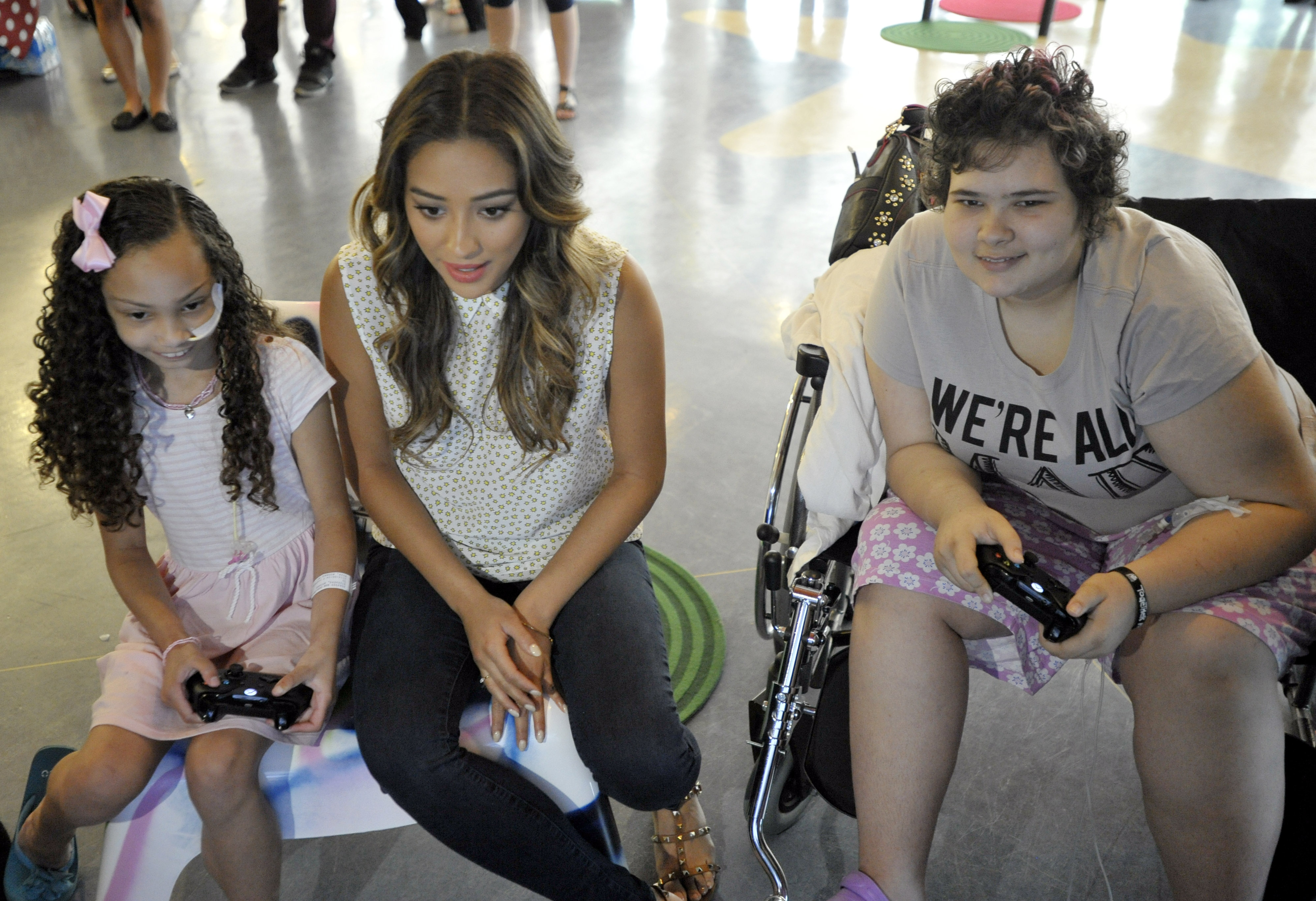 """Actress Shay Mitchell plays with young patients at The Hospital for Sick Children (SickKids) """"Pop-Up Arcade"""" powered by Duracell, on Monday June 23, 2014. The arcade is part of Duracell's """"Powering Smiles"""" program, which helps kids to be kids, even in the midst of illness. (Photo: Business Wire)"""