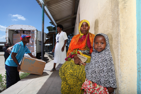 Mother Nasra Ally and child are waiting outside a clinic in the Northern Zonal Area of Tanzania's Dar es Salam District as a truck offloads medicine directly to the clinic. They await medical care that was not easily accessible prior to the launch of Project Last Mile. (Photo: Business Wire)