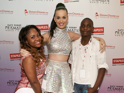"""Global pop star Katy Perry with local students Tiara Brooks, left, and Jaylin Barber, right, backstage at the Philips Arena during her Prismatic World Tour performance on Saturday, June 28, 2014, in Atlanta, GA. As part of its $1 million dollar donation to online charity DonorsChoose.org, Staples announced it has fully-funded the balance of every project on DonorsChoose.org in the Atlanta, GA community. This $128,158 donation helped 77 teachers fulfill classroom needs and helped more than 8,779 students in the Atlanta public school district. Katy Perry teamed up with Staples and DonorsChoose.org to """"Make Roar Happen"""" and support teachers during this back-to-school season. (Photo by Dan Harr/Invision for Staples/AP Images)"""