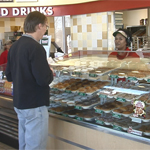 Broll of customers ordering and purchasing Krispy Kreme doughnuts