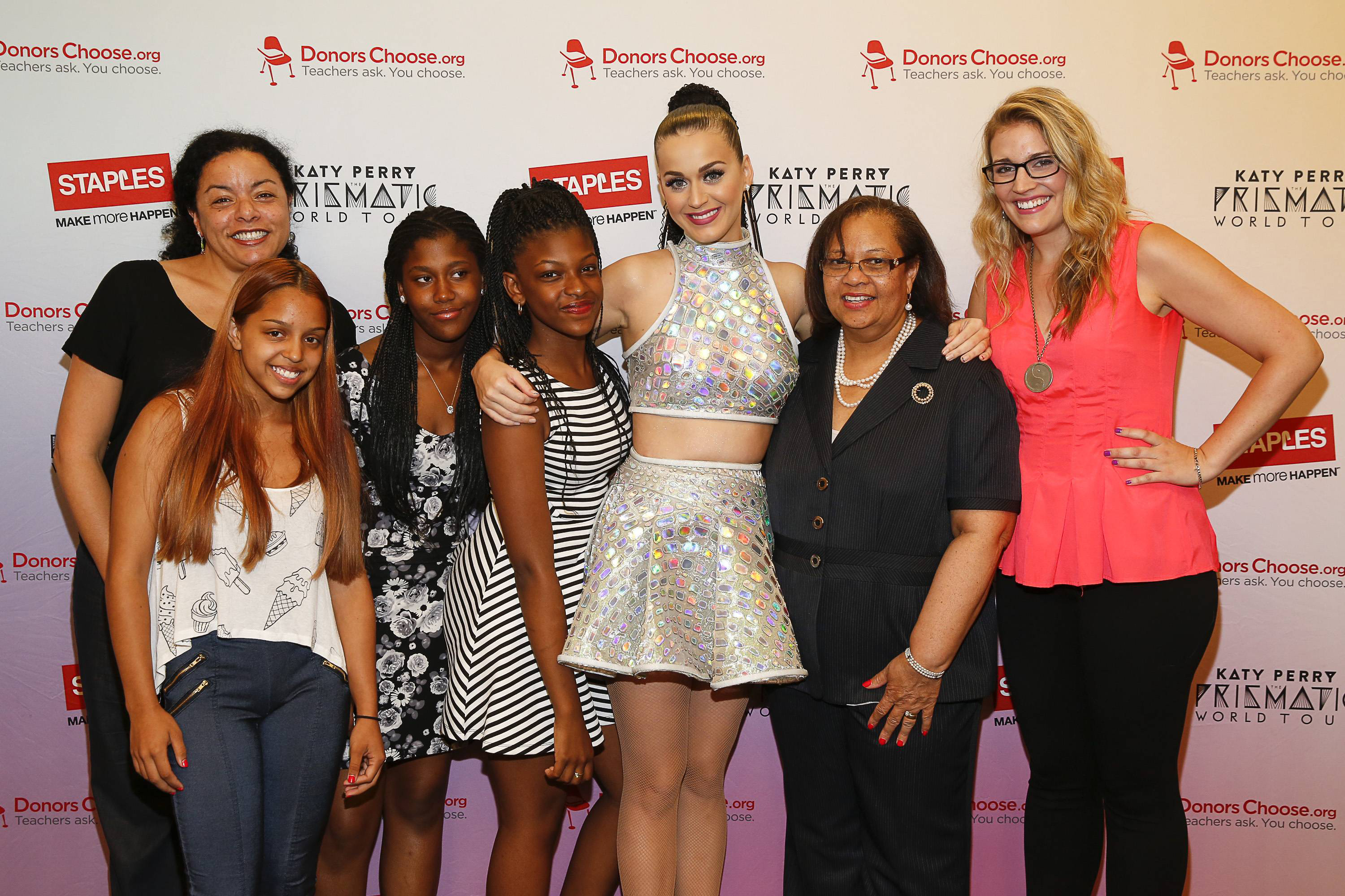 """Global pop star Katy Perry, center, meets with local teachers, left to right, Christine Foyer, local student Krysten Martinez, Dorothy Toure, Jahnay Bryan, Chancelor Dorita Gibson, and local teacher Jennifer Nelson backstage at Madison Square Garden during her Prismatic World Tour performance on Wed., July 9 in New York, N.Y. Staples teamed up with superstar Katy Perry to """"Make Roar Happen"""" and celebrate and support teachers during the back-to-school season by donating $1 million to DonorsChoose.org, a charity that has helped fund more than 450,000 classroom projects for teachers and impacted more than 11 million students. (Photo by Mark Von Holden/Invision for Staples/AP Images)"""