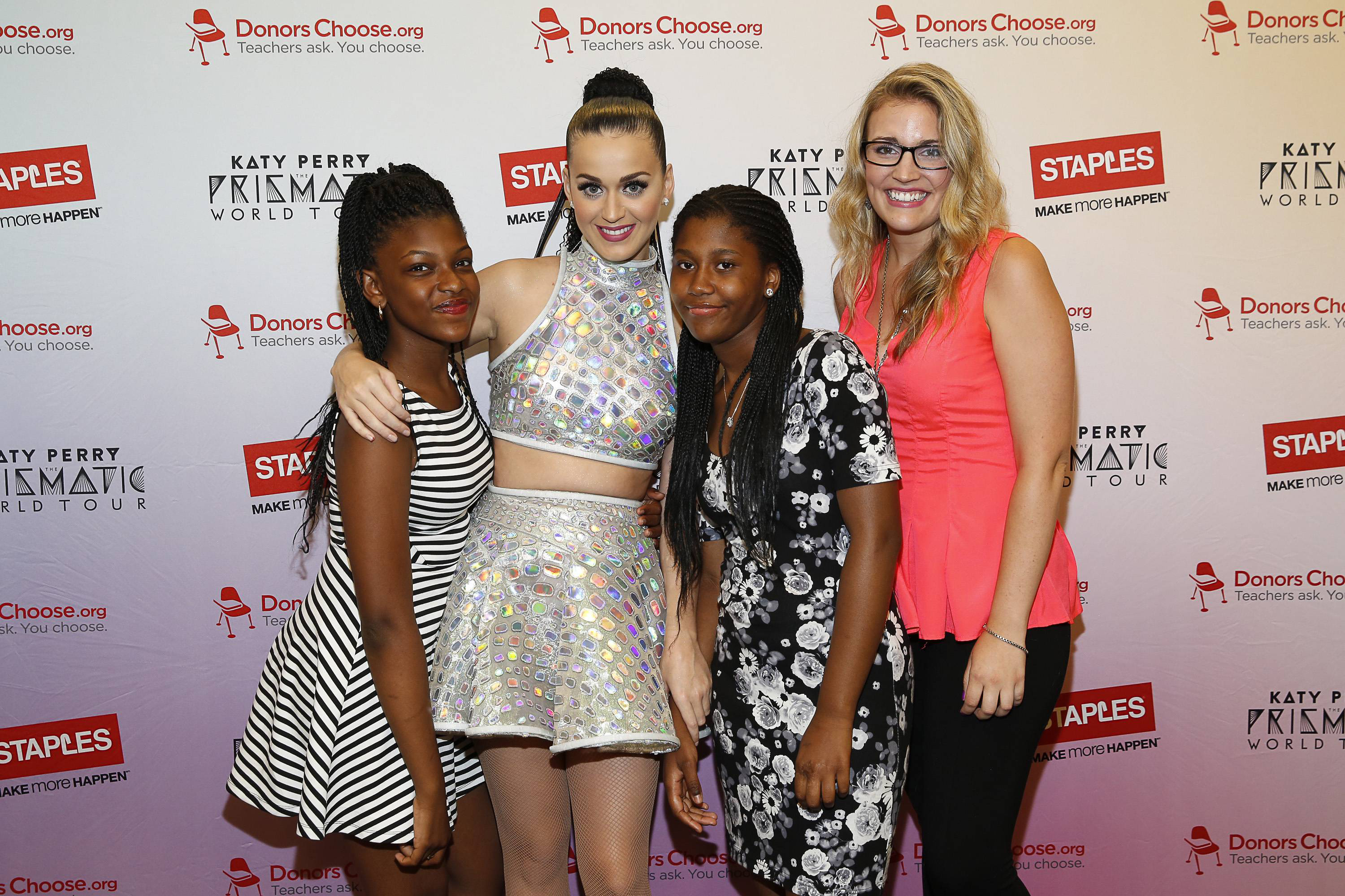 """Global pop star Katy Perry, center, meets with local students, left to right, Jahnay Bryan, Dorothy Toure, and local teacher Jennifer Nelson backstage at Madison Square Garden during her Prismatic World Tour performance on Wed., July 9 in New York, N.Y. Staples teamed up with superstar Katy Perry to """"Make Roar Happen"""" and celebrate and support teachers during the back-to-school season by donating $1 million to DonorsChoose.org, a charity that has helped fund more than 450,000 classroom projects for teachers and impacted more than 11 million students. (Photo by Mark Von Holden/Invision for Staples/AP Images)"""