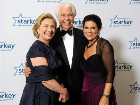 "Former U.S. Secretary of State Hillary Rodham Clinton poses for a picture with Starkey Hearing Foundation founders Bill and Tani Austin at the Starkey Hearing Foundation's ""So the World May Hear"" Awards Gala on Sunday, July 20, 2014 in St. Paul, Minn. The foundation is a member of the Clinton Global Initiative and gives away more than 100,000 hearing aids in the U.S. and around the world annually. (Photo by Diane Bondareff/Invision for Starkey Hearing Foundation/AP Images)"