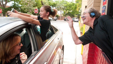 Colorful soccer commentator Ray Hudson poses for a selfie with Frances Thomas, top left, with her mom Angela looking on, as Ray surprised fans at the drive thru at a DQ Grill & Chill Restaurant during the launch of the new Chips Ahoy Blizzard Treat on Tuesday, July 29, 2014 in Fort Lauderdale, Fla. (Photo: Business Wire)