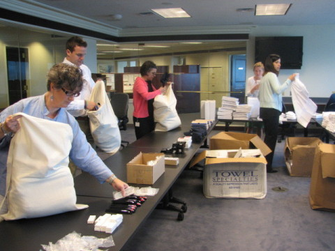 Volunteers from Loomis, Sayles & Co. assemble care packages for uAspire Last Dollar Scholarship recipients on July 29, 2014. (Photo: Business Wire)