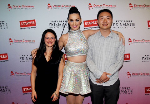 """Global pop star Katy Perry, center, with local teachers, left to right, Amanda Robb and Yu Chen backstage at the TD Garden during her Prismatic World Tour performance on Fri., Aug 1 in Boston, Mass. Staples teamed up with superstar Katy Perry to """"Make Roar Happen"""" and support teachers during the back-to-school season by donating $1 million to DonorsChoose.org, a charity that has helped fund more than 450,000 classroom projects for teachers and impacted more than 11 million students. (Photo by Marc Andrew Deley/Invision for Staples/AP Images)"""