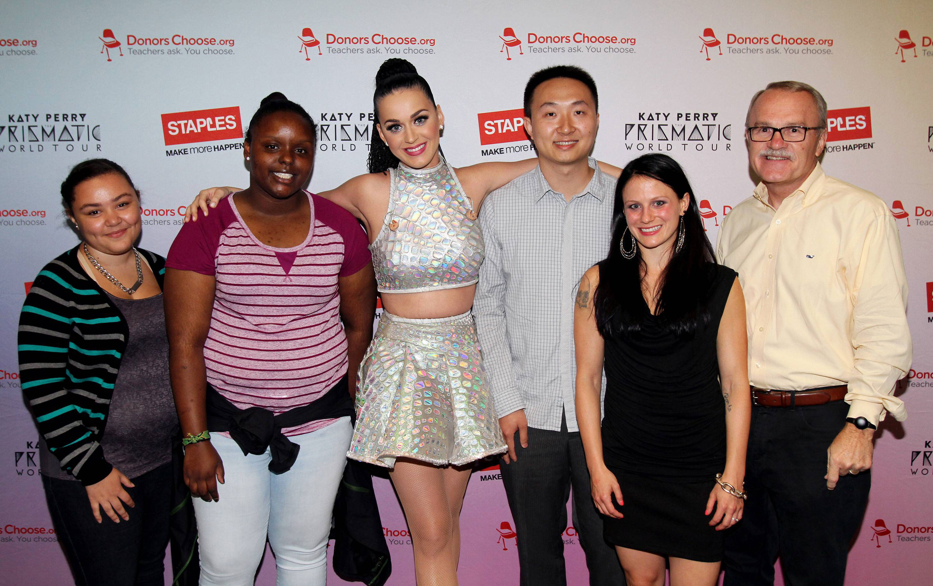 """Global pop star Katy Perry, center, with local teachers, students and CEO and Chairman, Staples, left to right, Tajia Reverdes, Janile Campbell, Yu Chen, Amanda Robb and Ronald Sargent backstage at the TD Garden during her Prismatic World Tour performance on Fri., Aug 1 in Boston, Mass. Staples teamed up with superstar Katy Perry to """"Make Roar Happen"""" and support teachers during the back-to-school season by donating $1 million to DonorsChoose.org, a charity that has helped fund more than 450,000 classroom projects for teachers and impacted more than 11 million students. (Photo by Marc Andrew Deley/Invision for Staples/AP Images)"""
