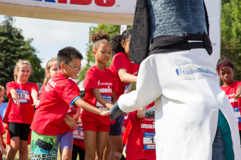 Rainer Vista Boys and Girls Club youth members Nathan Dang (front left) and Jaicieonna Gero-Holt (front center) of Seattle give high-fives to UnitedHealthcare's Dr. Health E. Hound before the start of the UnitedHealthcare IRONKIDS Seattle Fun Run, which took place in Genesee Park on Saturday, August 16. (Photo Source: Trig Jones)