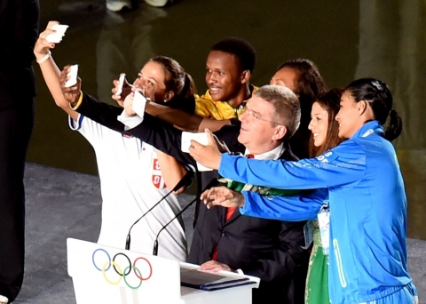 Picture A: Thomas Bach, the IOC President, invites some of the young athletes to use their smart pho ...