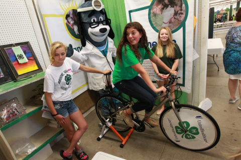 """4-H Youth Health Ambassador Rose Rella of Central Valley, N.Y., creates her own smoothie using pedal power at the annual New York State Fair in Geddes, near Syracuse, on Aug. 21. The smoothie bikes are part of 4-H and UnitedHealthcare's partnership called """"Eat4-Health,"""" which helps tackle obesity by promoting healthy eating and lifestyles among youth and families. With her, from left, is Kristal Spencer, of Binghamton, UnitedHealthcare mascot Dr. Health E. Hound and April Turner of Central Valley (Photo: Michael J. Okoniewski for UnitedHealthcare)."""