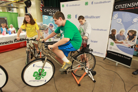 "4-H Youth Health Ambassadors Zaia Ivan from Greene, N.Y. (left), and Nate Edwards from Morris, N.Y. (center), create their own smoothies using pedal power at the annual New York State Fair in Geddes, near Syracuse, on Aug. 21. The smoothie bikes are part of 4-H and UnitedHealthcare's partnership called ""Eat4-Health,"" which helps tackle obesity by promoting healthy eating and lifestyles among youth and families (Photo: Michael J. Okoniewski for UnitedHealthcare)."